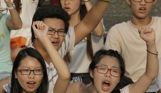 Students wave their fists during a rally at the Chinese University of Hong Kong campus in Hong Kong, Monday, Sept. 22, 2014. Thousands of Hong Kong students boycotted classes Monday to protest Beijing's decision to restrict electoral reforms in a weeklong strike marking the latest phase in the battle for democracy in the southern Chinese city. (AP Photo/Vincent Yu)