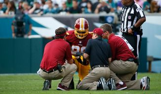Personnel check on Washington Redskins' Brian Orakpo after an injury during the second half of an NFL football game against the Philadelphia Eagles, Sunday, Sept. 21, 2014, in Philadelphia. (AP Photo/Matt Rourke)