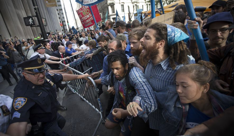 Protestors and police wrestle near a barricade on the corner of Wall Street and Broadway during a march demanding action on climate change and corporate greed, Monday, Sept. 22, 2014, a day after a huge climate march in New York. (AP Photo/John Minchillo)