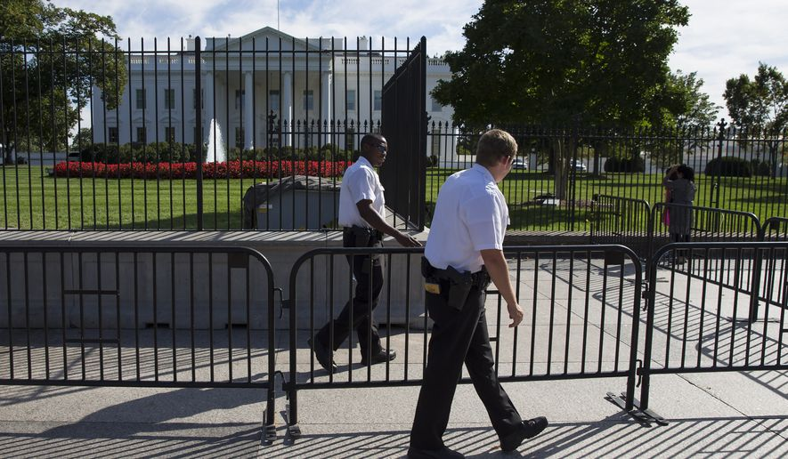 "Secret Service police officers walk outside the White House in Washington, Monday, Sept. 22, 2014. Earlier, President Barack Obama said the Secret Service does ""a great job."" He says he is grateful for the ""sacrifices"" the service performs on his behalf and on behalf of his family. Obama made his comments Monday in the aftermath of Friday's security breach, when an intruder managed to jump the north fence of the White House and escape capture until he was inside the North Portico entrance of the presidential mansion. (AP Photo/Evan Vucci)"