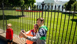 Tourists take a camera phone photograph of themselves along Pennsylvania Avenue outside the White House in Washington, D.C., in this Monday, Sept. 22, 2014, file photo. (Andrew Harnik/The Washington Times)