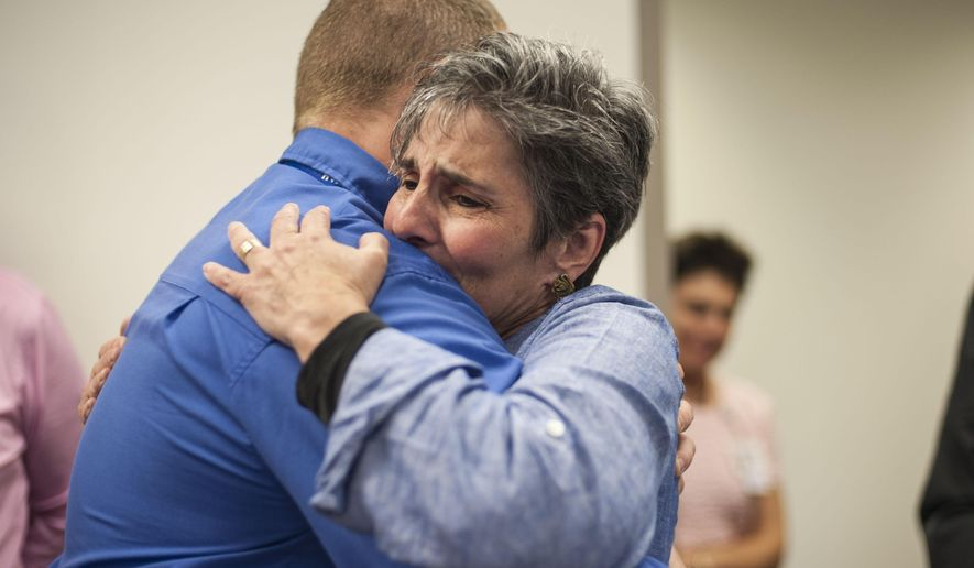 In this Wednesday, Sept. 17, 2014 photo, Karen Grahams of Ypsilanti, Mich. hugs EMT Dispatcher Tim Wilson as she and her husband, Robert, visit the Huron Valley Ambulance Call Center in Ann Arbor, Mich. Over the phone, Wilson helped Robert save Karen's life, teaching him how to perform chest compressions after she stopped breathing and went into cardiac arrest. (AP Photo/The Ann Arbor News - MLive.com, Katie McLean)
