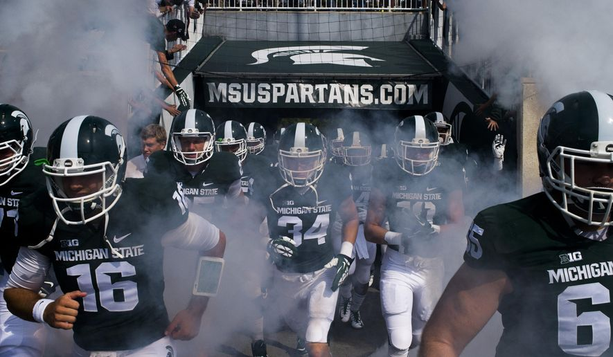 Michigan State's Tommy Vento, left, runs alongside his teammates as they take the field through a screen of smoke before playing Eastern Michigan on Saturday, Sept. 20, 2014 at Spartan Stadium in East Lansing, Mich. (AP Photo/The Flint Journal, Jake May)