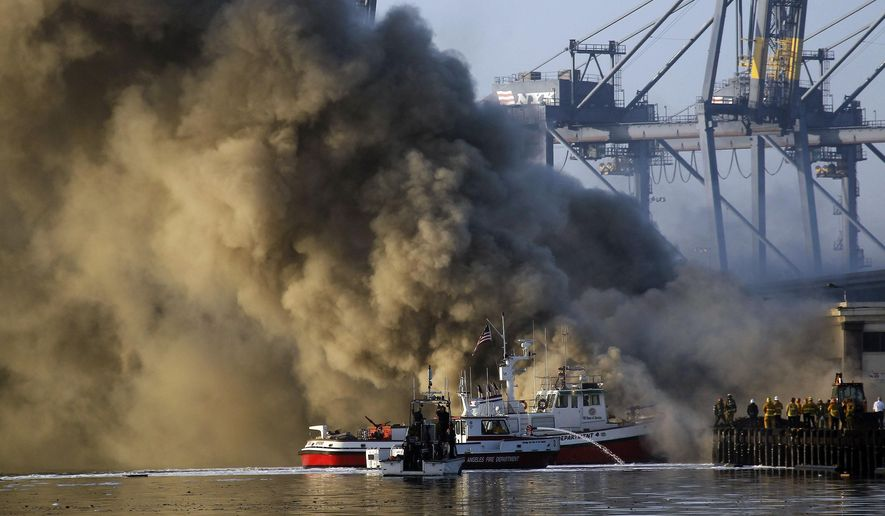 Los Angeles Firefighters watch as smoke from a dock fire rises at the Port of Los Angeles in the Wilmington section of Los Angeles on Tuesday, Sept 23, 2014. The fire that forced evacuations from the wharf continues to smolder but officials say it's under control. Nearly 12 hours after starting, the blaze is sending up huge plumes of smoke that is drifting over Los Angeles Harbor early Tuesday. (AP Photo/ Nick Ut )