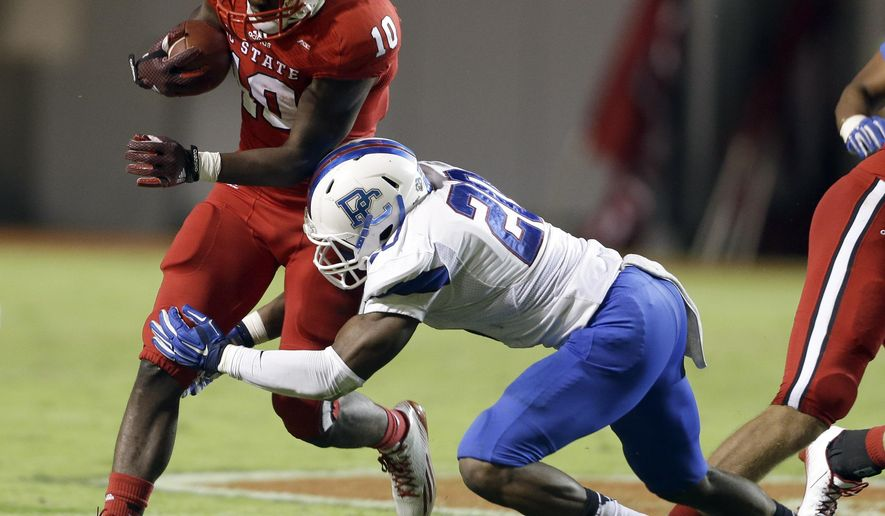 North Carolina State's Shadrach Thornton (10) breaks a tackle against Presbyterian's Cory White (20) and runs for a touchdown during the second half of an NCAA college football game in Raleigh, N.C., Saturday, Sept. 20, 2014. North Carolina State won 42-0. (AP Photo/Gerry Broome)
