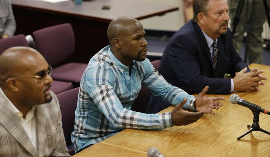 "Boxer Floyd Mayweather Jr., center, appears with attorney Shane Emerick, right, and Leonard Ellerbe before the Nevada Athletic Commission Tuesday, Sept. 23, 2014, in Las Vegas. Mayweather appeared before the commission to answer questions about scenes aired on the reality show ""All Access"" prior to his fight against Marcos Maidana earlier this month. (AP Photo/John Locher)"