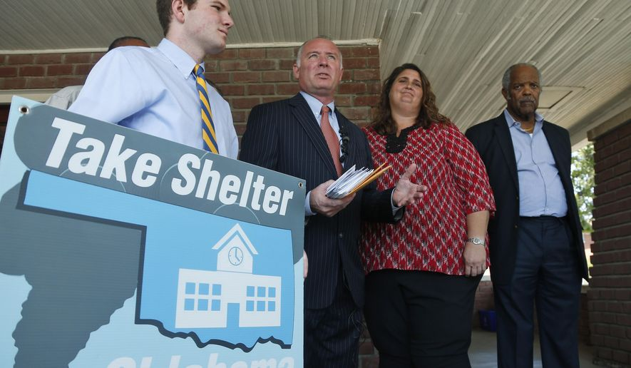Logan Slane, left, a senior at South Moore High School, holds a Take Shelter Oklahoma sign during a news conference held by supporters of an initiative petition to place storm shelters in every Oklahoma public school, in Oklahoma City, Tuesday, Sept. 23, 2014. From left are Logan Slane, his father, Oklahoma City attorney David Slane,  who represents the organization, Danni Legg, the mother of tornado victim Christopher Legg, and Pastor John A. Reed Jr. (AP Photo/Sue Ogrocki)