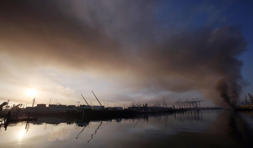 A plume of smoke rises from a dock fire at the Port of Los Angeles in the Wilmington section of Los Angeles on Tuesday, Sept 23, 2014. The Los Angeles Fire Department says a spark from a welder's torch caused the fire that forced about 850 workers to evacuate the area Monday night. (AP Photo/ Nick Ut )