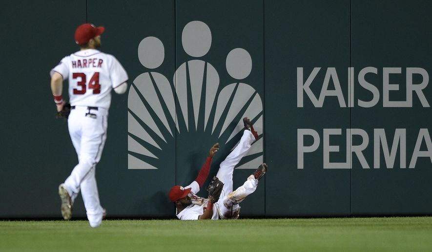 Washington Nationals center fielder Denard Span, right, comes to a stop against the outfield wall after he caught a line drive by New York Mets left fielder Matt den Dekker and tumbled during the third inning of a baseball game, Tuesday, Sept. 23, 2014, in Washington. Washington Nationals left fielder Bryce Harper (34) is at left. (AP Photo/Nick Wass)