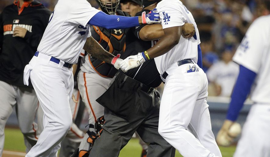 Los Angeles Dodgers' Yasiel Puig, right, is restrained by home plate umpire Adrian Johnson, center, and teammate Matt Kemp as he charges toward San Francisco Giants starting pitcher Madison Bumgarner after he was hit by a pitch during the first inning of a baseball game Tuesday, Sept. 23, 2014, in Los Angeles. (AP Photo/Jae C. Hong)