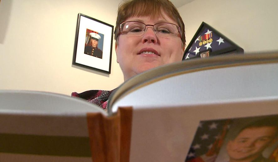 In this image taken from video, Lisa Riley, mother of retired Marine Jordan Buisman who suffered from epilepsy, holds a photo album about her son in Clear Lake, Minn.  Department of Veterans Affairs medical records show that Buisman called the Minneapolis VA Health Care System to reschedule a medical exam four days after his death. Buisman's family believes his data was falsified to hide delays in patient care, and they've filed a wrongful death claim against the VA, KARE-TV reported Monday night, Sept. 22, 2014. (AP Photo/KARE-TV)