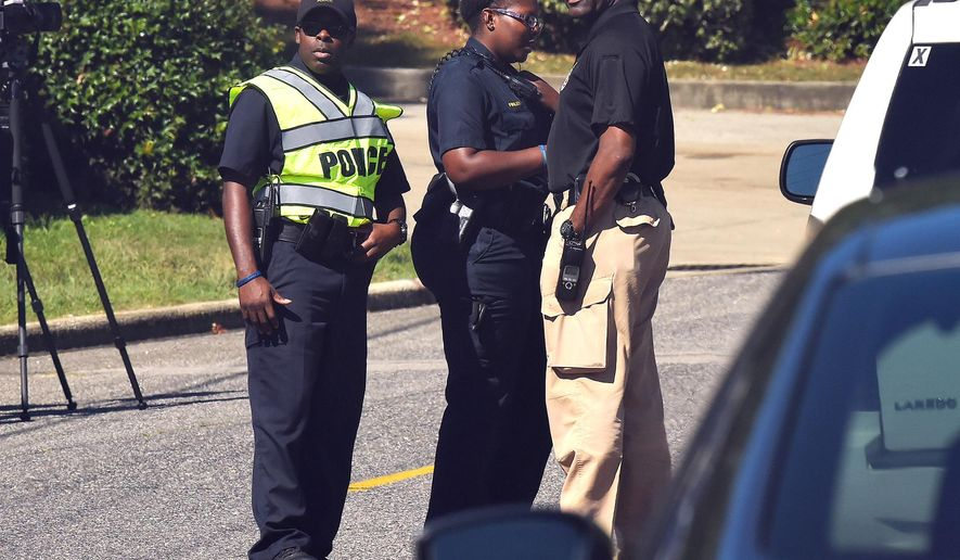 Police officers confer near the scene where three people were killed, including the gunman, at a UPS facility in Birmingham, Ala., Tuesday, Sept. 23, 2014. (AP Photo/AL.com, Joe Songer) MAGS OUT