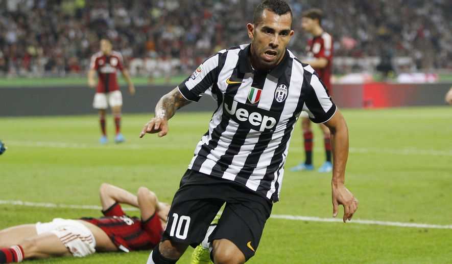 Juventus's Carlos Tevez celebrates after scoring during the Serie A soccer match between AC Milan and Juventus at the San Siro stadium in Milan, Italy, Saturday, Sept. 20, 2014. (AP Photo/Antonio Calanni)