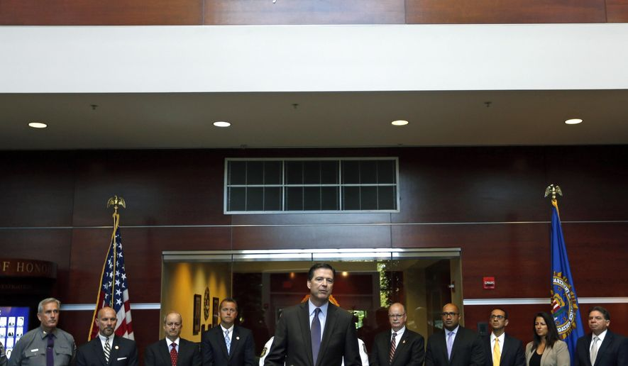 Federal Bureau of Investigation Director James Comey, joined by local law enforcement officials, speaks during a news conference at the FBI Albany Field Office on Tuesday, Sept. 23, 2014, in Albany, N.Y. (AP Photo/Mike Groll)