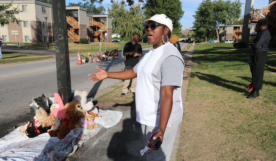 A woman gestures by a new teddy bear memorial on Tuesday, Sept. 23, 2014, in Ferguson, Mo., near the spot of where Michael Brown was shot by Ferguson police office Darren Wilson on Aug. 9.  The original teddy bear memorial was destroyed by fire earlier Tuesday morning. Ferguson police spokesman Devin James says the cause of the fire is under investigation. (AP Photo/St. Louis Post-Dispatch,  David Carson)  EDWARDSVILLE INTELLIGENCER OUT; THE ALTON TELEGRAPH OUT