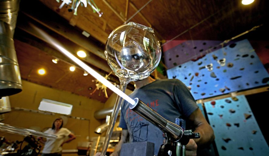In this Aug. 28, 2014 photo, glass artist Jonathan Davis shapes a piece of glass while working on a sculpture at his rural studio near Pittsboro, N.C. (AP Photo/Gerry Broome)