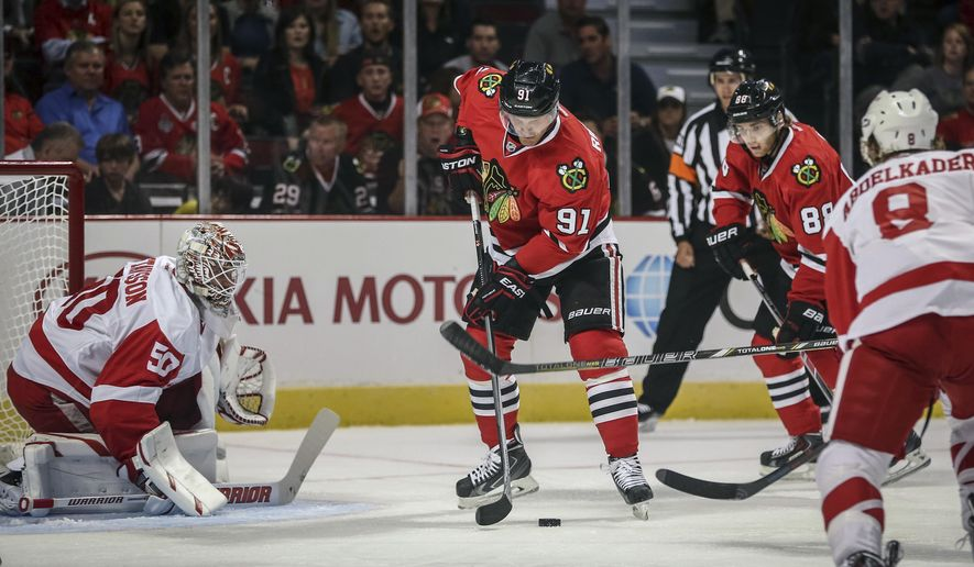 CORRECTS LAST NAME TO RICHARDS FROM RICHARDSON - Chicago Blackhawks' Brad Richards (91) tries to control the puck in front of Detroit Red Wings goalie Jonas Gustavsson in an NHL exhibition hockey game in Chicago on Tuesday, Sept. 23, 2014. (AP Photo/Charles Cherney)