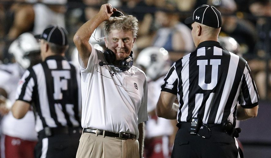 South Carolina head coach Steve Spurrier talks with umpire Tom Quick, right, during the second quarter of an NCAA college football game against Vanderbilt Saturday, Sept. 20, 2014, in Nashville, Tenn. (AP Photo/Mark Humphrey)