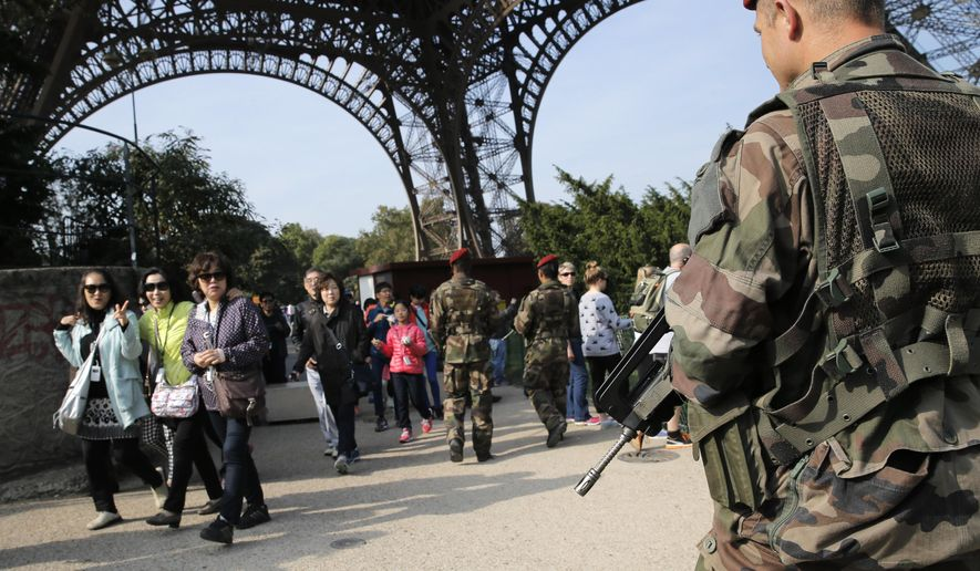 Soldiers patrol at the Eiffel Tower in Paris, France, Tuesday, Sept. 23, 2014. Frenchman Herve Gourdel, 55,  was abducted in Algeria on Monday by a splinter group from al-Qaida's North African branch. The Jund al-Khilafah, or Soldiers of the Caliphate, said it would kill him unless France halts it airstrikes in Iraq within 24 hours. French forces on Friday joined the U.S. in carrying out airstrikes against extremists who have overrun large areas of Syria and Iraq. (AP Photo/Christophe Ena)