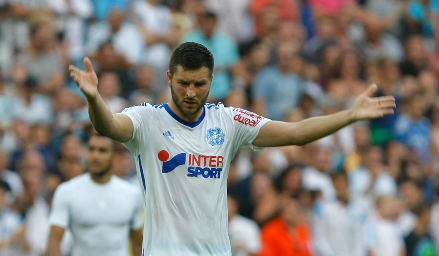 Marseille's French forward Andre-Pierre Gignac  gestures to supporters at the end of their League One soccer match against Rennes, at the Velodrome Stadium, in Marseille, southern France, Saturday, Sept. 20, 2014. (AP Photo/Claude Paris)