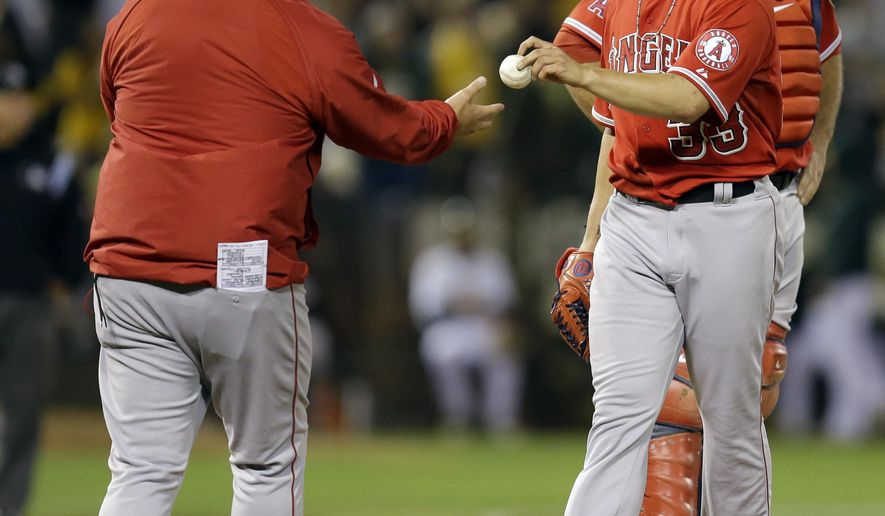 Los Angeles Angels' C.J. Wilson, right, hands the ball to manager Mike Scioscia as he is removed from the  baseball game against the Oakland Athletics in the first inning Monday, Sept. 22, 2014, in Oakland, Calif. (AP Photo/Ben Margot)