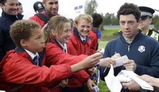 Europe's Rory McIlroy signs autographs for fans as he walks to the 16th tee during a practice round ahead of the Ryder Cup golf tournament at Gleneagles, Scotland, Tuesday, Sept. 23, 2014. (AP Photo/Matt Dunham)
