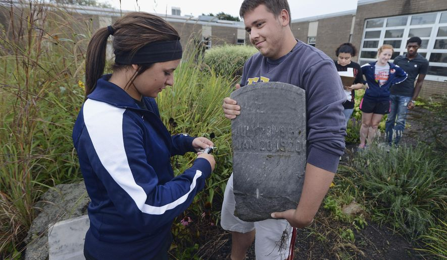 In this Sept. 9, 2014 photo, Pontiac Township High School seniors Katie Kujka and Ethan Putnam demonstrate some of the work they are doing on a project at St. Paul Cemetery in Odell, Ill., in which they are helping to document the seven headstones marking the graves of Civil War soldiers. (AP Photo/The Pantagraph, Steve Smedley)