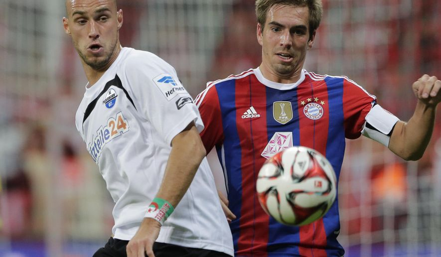 Paderborn's Daniel Brueckner, left, and Bayern's Philipp Lahm challenge for the ball during the German first division Bundesliga soccer match between FC Bayern and SC Paderborn 07 in the Allianz Arena in Munich, Germany, on Tuesday, Sept. 23, 2014. (AP Photo/Matthias Schrader)
