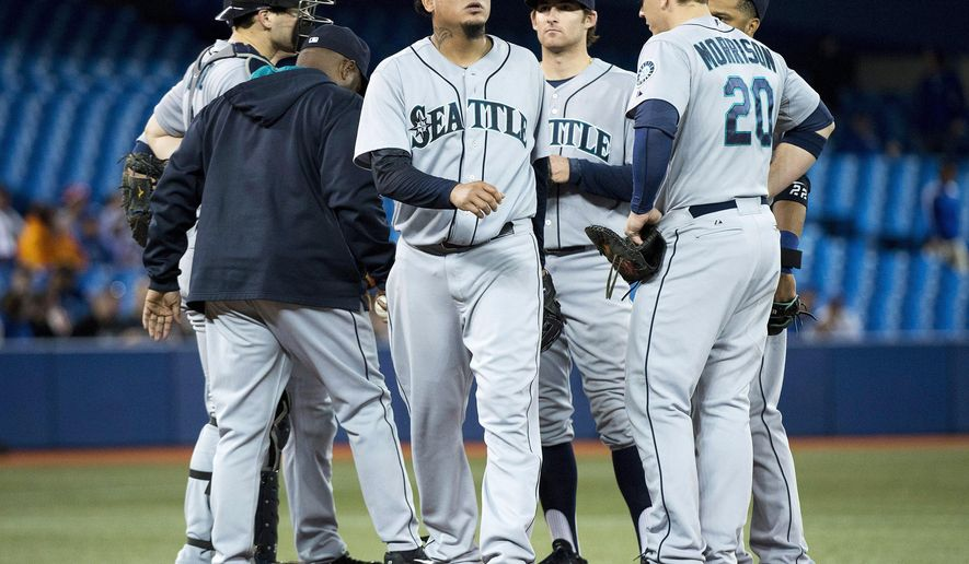 Seattle Mariners starting pitcher Felix Hernandez, center, leaves the mound after being pulled from the game against the Toronto Blue Jays during the fifth inning of a baseball game in Toronto on Tuesday, Sept, 23, 2014. (AP Photo/The Canadian Press, Nathan Denette)