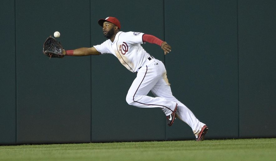 Washington Nationals center fielder Denard Span lunges to make a catch on a line drive ball by New York Mets' Matt den Dekker during the third inning of a baseball game, Tuesday, Sept. 23, 2014, in Washington. (AP Photo/Nick Wass)