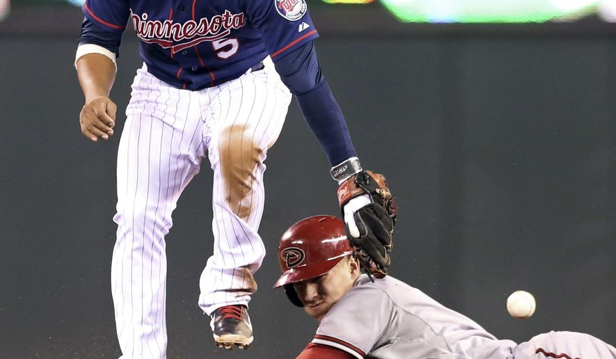 Arizona Diamondbacks' Jake Lamb, right, doubles as Minnesota Twins shortstop Eduardo Escobar can't get a handle on the ball in the fourth inning of a baseball game, Tuesday, Sept. 23, 2014, in Minneapolis. (AP Photo/Jim Mone)