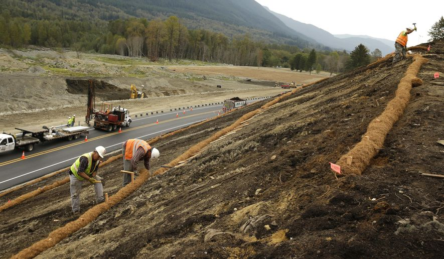 Workers put erosion-prevention measures in place above the rebuilt road between Darrington, Wash., and Arlington, Wash., that was wiped out by the devastating mudslide that killed 43 people last March in the community of Oso, Wash., Tuesday, Sept. 23, 2014. The road re-opened Monday night to two-way, 50 mph traffic. The highway was realigned and raised as much as 20 feet in places. Crews also installed six new culverts. (AP Photo/Ted S. Warren)