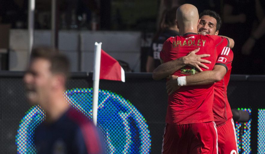 Toronto FC 's Gilberto, right, celebrates with Michael Bradley after scoring against Chivas USA during the first half of an MLS soccer game in Toronto on Sunday, Sept. 21, 2014. (AP Photo/The Canadian Press, Chris Young)