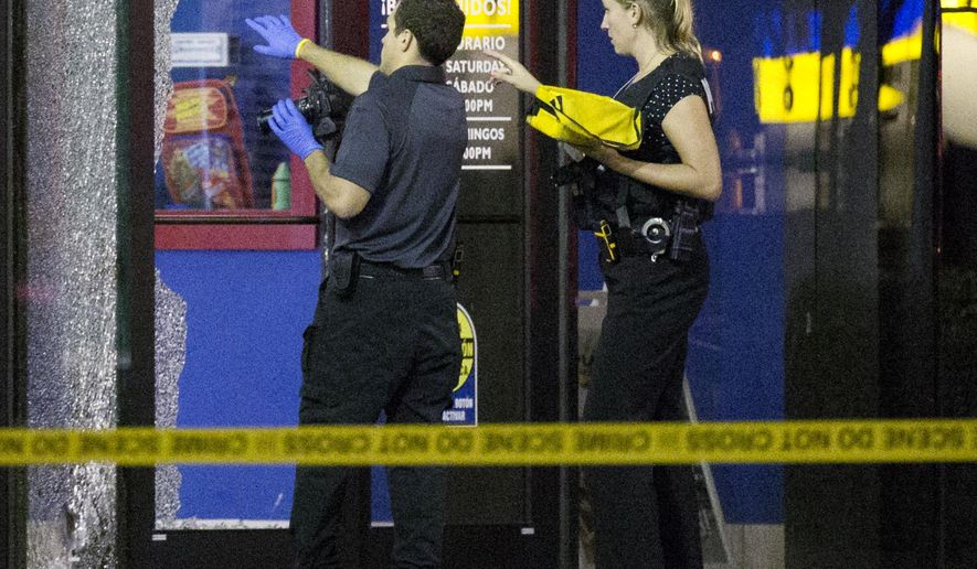 Crime scene technicians work outside a shopping mall where a shooting took place, Tuesday, Sept. 23, 2014, in Kissimmee, Fla. Authorities are trying to determine if two men found dead a short time later in a crashed vehicle were connected to the shooting. (AP Photo/John Raoux)