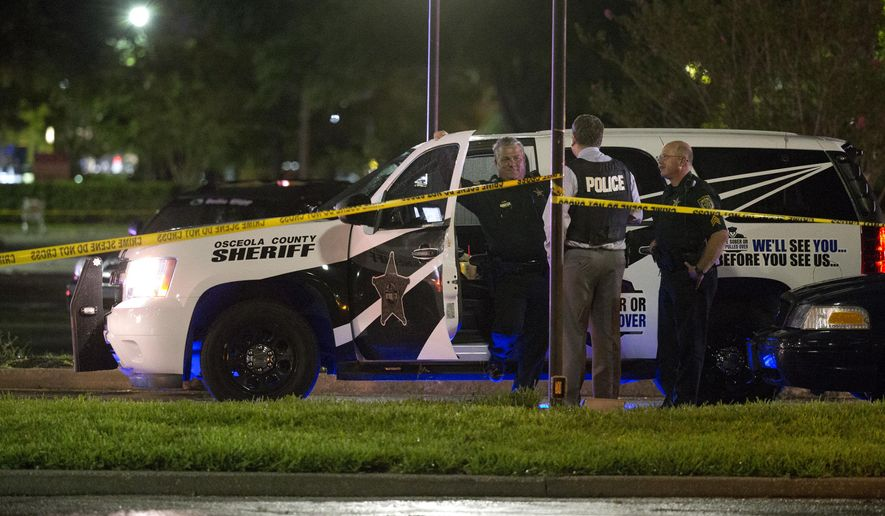 Law enforcement officers from the Kissimmee Police Department and the Osceola Sheriff's Office work a crime scene outside a shopping mall where a shooting took place, Tuesday, Sept. 23, 2014, in Kissimmee, Fla. Authorities are trying to determine if two men found dead a short time later in a crashed vehicle were connected. (AP Photo/John Raoux)