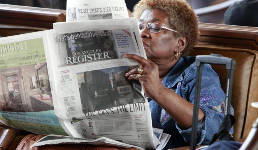 FILE - In this April 16, 2014 file photo, Dorothy Shumrt reads the Los Angeles Register newspaper on the day of it's launch while waiting for a train at Union Station, in Los Angeles. The Los Angeles Register, which debuted in April as a challenger to the Los Angeles Times, has ceased publication. Freedom co-owners Aaron Kushner and Eric Spitz sent a memo to employees Monday night, Sept. 22, 2014, announcing that the LA Register was closing. In announcing the closure, Freedom Communications Inc. also said it had sold the Santa Ana headquarters for its flagship paper, the Orange County Register, for $27 million to local developer Michael Harrah.  (AP Photo/Richard Vogel, File)