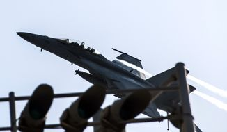 In this image provided by the U.S. Navy a F/A-18F Super Hornet attached to the Fighting Black Lions of Strike Fighter Squadron flies over the aircraft carrier USS George H.W. Bush in the Persian Gulf on Tuesday, Sept. 23, 2014, after conducting strike missions against Islamic State group targets in Syria. (AP Photo/U.S. Navy, Mass Communication Specialist 3rd Class Brian Stephens)