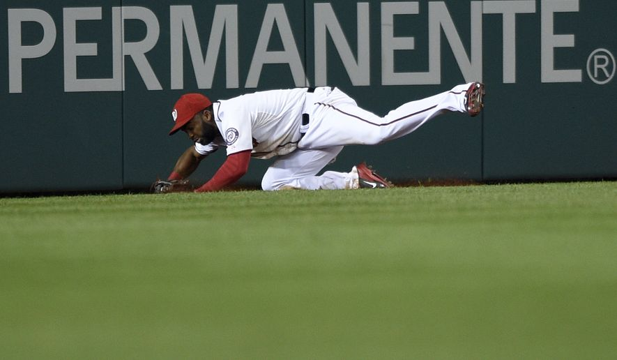 Washington Nationals center fielder Denard Span tumbles on the ground after he caught a line drive by New York Mets left fielder Matt den Dekker2 during the third inning of a baseball game, Tuesday, Sept. 23, 2014, in Washington. The Nationals won 4-2. (AP Photo/Nick Wass)