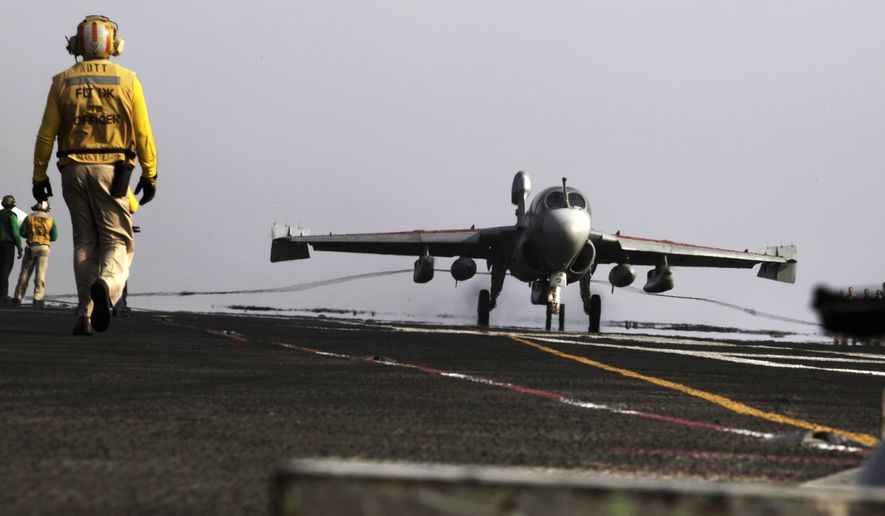 In this Aug. 10, 2014, photo, an aircraft for missions targeting the Islamic State group in Iraq lands at the USS George H.W. Bush in the Persian Gulf. Combined U.S.-Arab airstrikes at the heart of the Islamic State group's military strongholds in Syria achieved their strategic aim of showing the extremists that their savage attacks will not go unanswered, the top American military officer said Tuesday, Sept. 23, 2014. (AP Photo/Hasan Jamali)