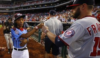 Taney Dragons' Mo'ne Davis, left, greets Washington Nationals' Kevin Frandsen after a tribute to celebrate the youth team's accomplishments at the Little League World Series before a baseball game between the Philadelphia Phillies and the Washington Nationals, Wednesday, Aug. 27, 2014, in Philadelphia. (AP Photo/Matt Slocum)
