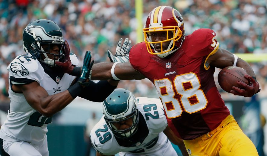 Washington Redskins' Pierre Garcon (88) tries to break a tackle by Washington Redskins' Tracy Porter (22) during the first half of an NFL football game, Sunday, Sept. 21, 2014, in Philadelphia. (AP Photo/Matt Rourke)