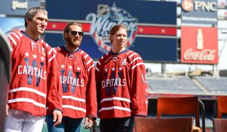 Washington Capitals Captain Alex Ovechkin, left, Center Nicklas Backstrom, right, and Goaltender Braden Holtby, second from left, show off their specially designed jerseys for the 2015 Bridgestone NHL Winter Classic held at Nationals Park, Washington, D.C., Tuesday, September 23, 2014. (Andrew Harnik/The Washington Times)