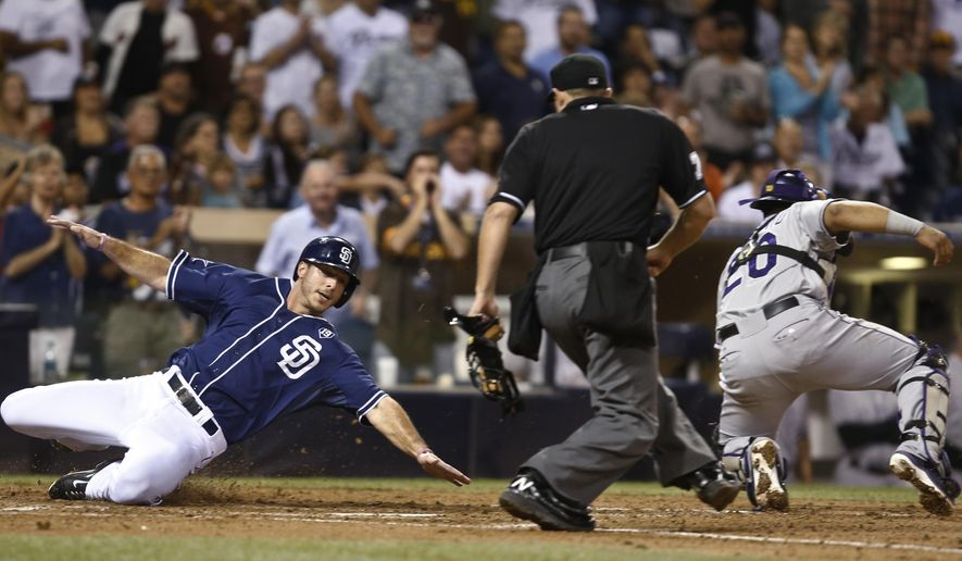 San Diego Padres' Tommy Medica reaches to touch home plate as Colorado Rockies catcher Wilin Rosario goes for the wide throw and umpire Tripp Gibson watches Medica score in the sixth inning of a baseball game Tuesday, Sept. 23, 2014, in San Diego.  (AP Photo/Lenny Ignelzi)