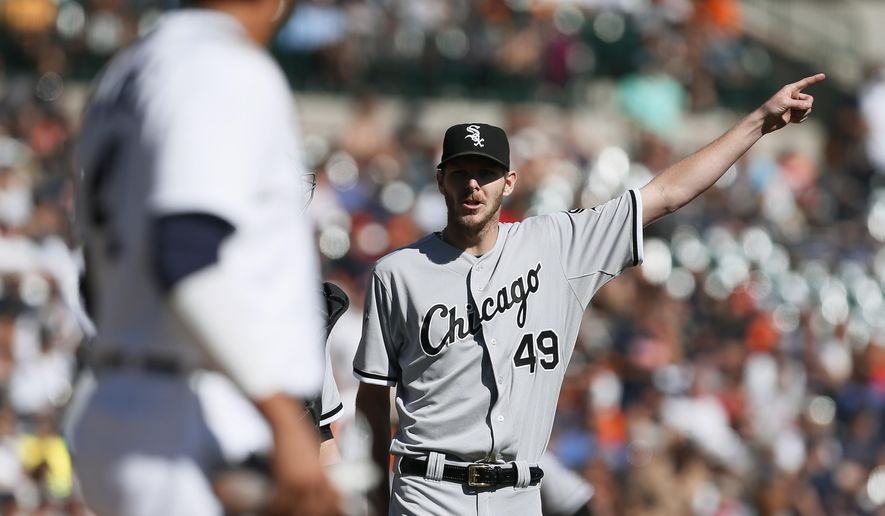 Chicago White Sox starting pitcher Chris Sale (49) points to the outfield while talking to Detroit Tigers' Victor Martinez, who was hit by the previous pitch, in the sixth inning of a baseball game in Detroit Wednesday, Sept. 24, 2014. (AP Photo/Paul Sancya)