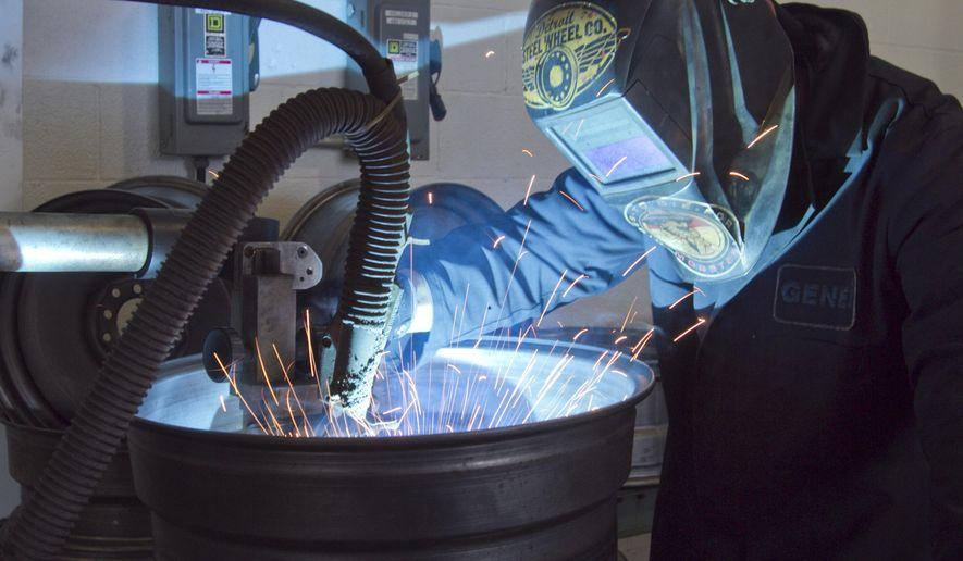 Mobsteel partner Steve Ryan welds a steel wheel in Detroit Steel Wheel, a spinoff of Mobsteel that makes customized steel wheels, Tuesday, Sept. 16, 2014. (AP Photo/Livingston County Daily Press & Argus, Gillis Benedict)
