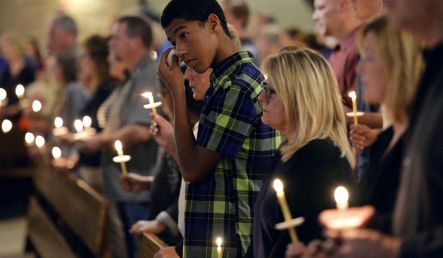 Community members and friends of missing North Dakota State University student Thomas Bearson grieve for him during a candlelight service Tuesday night, Sept. 23, 2014 at St. Francis Xavier Catholic Church in Sartell, Minn. (AP Photo/St. Cloud Times, Kimm Anderson)
