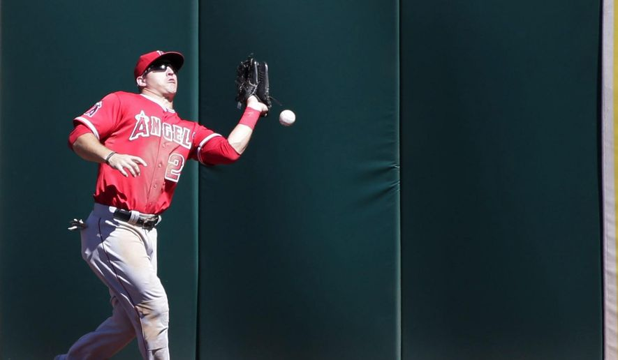 Los Angeles Angels center fielder Mike Trout drops a fly ball from Oakland Athletics' Josh Donaldson during the fourth inning of a baseball game on Wednesday, Sept. 24, 2014, in Oakland, Calif.  Donaldson reached third base on the play. (AP Photo/Marcio Jose Sanchez)