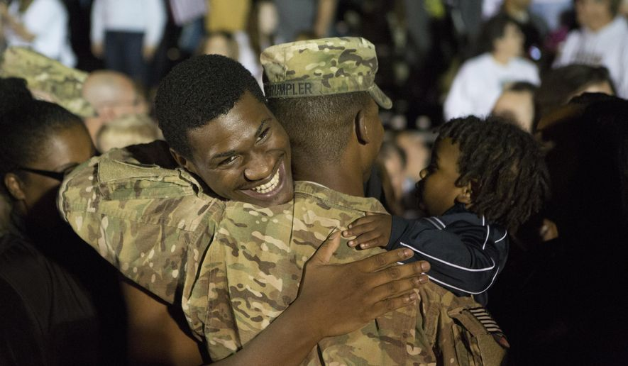 Stefan Sims hugs his friend Daniel Crumpter after the welcome home ceremony for the 1460th Transport Company at H.H. Dow High School in Midland, Tuesday Sept. 23, 2014. (AP Photo/The Saginaw News, Coty Giannelli)