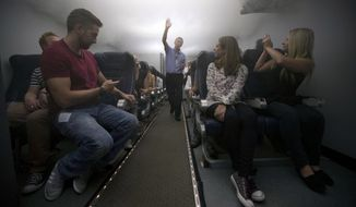 In this Sept. 10, 2014 photo, British Airways flight safety instructor Andy Clubb, center, instructs participants as theatrical smoke begins to fill the cabin simulator during a British Airways flight safety course at the airline's Cranebank training facility, near Heathrow airport in London. The half-day safety course, now open to frequent fliers willing to pay $265, encourages passengers to be aware of their surroundings and familiarize themselves with what happens in an emergency. (AP Photo/Matt Dunham)