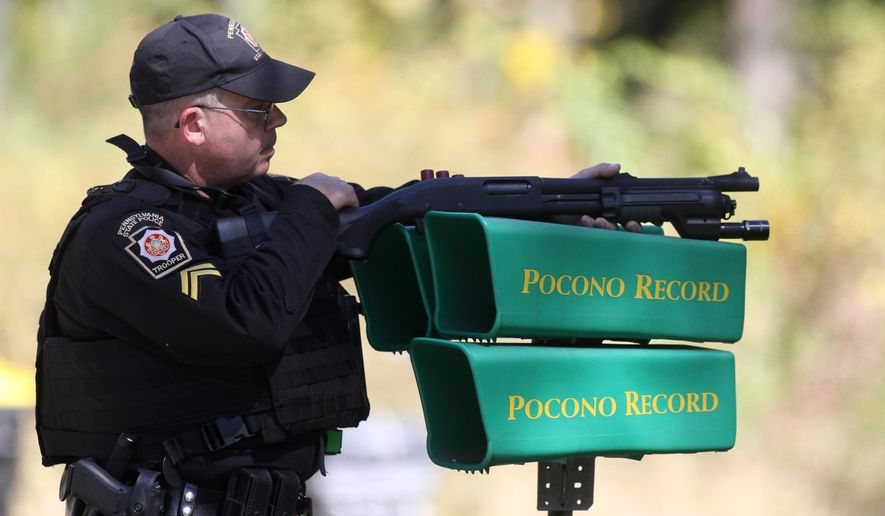 A Pennsylvania State Police trooper helps create a perimeter in the search area for accused cop killer Eric Frien near the intersection of Happy Hill Lane and Bear Town Road in Canadensis, Pa., on Tuesday, Sept. 23, 2014. (AP Photo/The Times-Tribune, Jake Danna Stevens)